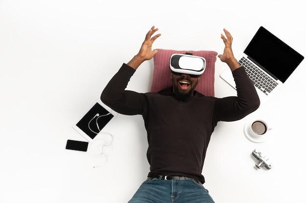 Homme afro-américain émotionnel à l'aide d'un casque vr entouré de gadgets isolés sur des technologies de surface blanche jouant émotionnel