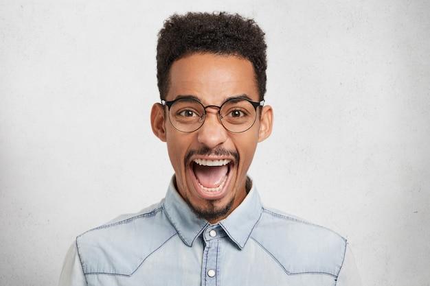 Homme afro-américain émotionnel dans des lunettes rondes, ouvre la bouche d'excitation, s'exclame joyeusement