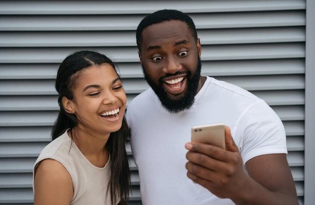 Homme afro-américain émotionnel et femme tenant un téléphone mobile, achats en ligne