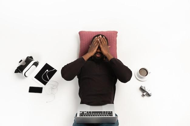 Homme afro-américain émotionnel utilisant un ordinateur portable entouré de gadgets isolés sur le mur blanc du studio.