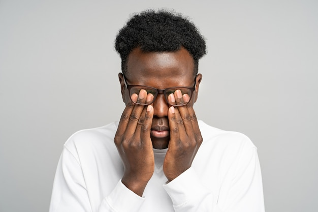 Homme afro-américain endormi dans des lunettes se frottant les yeux, se sent fatigué après avoir travaillé sur un ordinateur portable