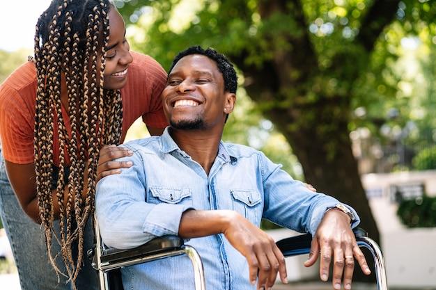 Un homme afro-américain en fauteuil roulant bénéficiant d'une promenade en plein air avec sa petite amie.
