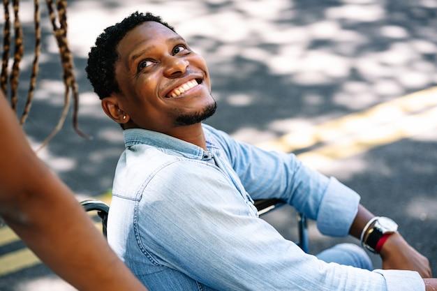 Un homme afro-américain en fauteuil roulant profitant d'une promenade à l'extérieur avec sa petite amie