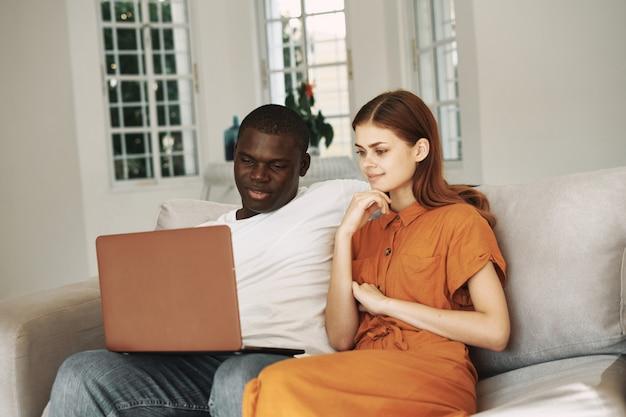 Homme afro-américain et femme blanche travaillant à domicile ordinateur portable indépendant, couple