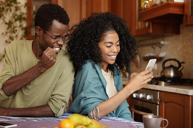 Homme afro-américain furieux et jaloux, serrant le poing de colère et de fureur tout en attrapant sa petite amie infidèle alors qu'elle envoie un message à son amant sur un téléphone mobile ayant une expression joyeuse et joyeuse