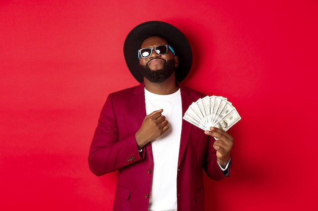 Homme afro-américain impertinent et cool en lunettes de soleil et chapeau, pointant sur lui-même et montrant des dollars, l'air confiant sur fond rouge