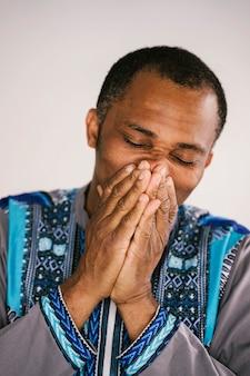 Homme afro-américain isolé couvrant sa bouche avec les mains. symptômes de dépression et de tristesse.