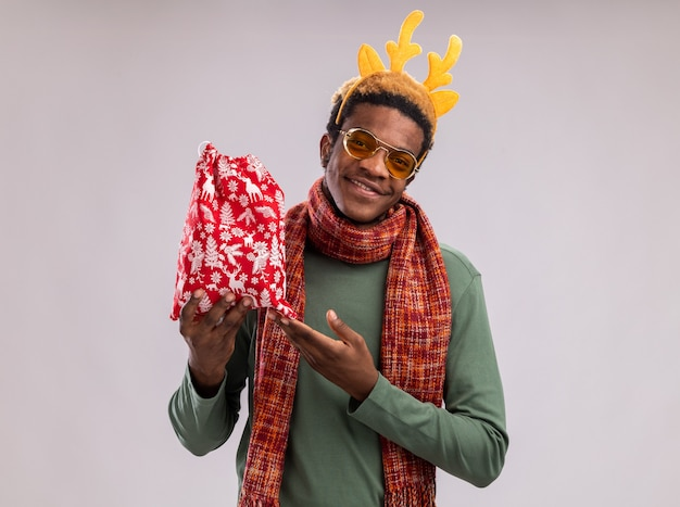 Homme afro-américain avec jante drôle avec des cornes de cerf et une écharpe autour du cou tenant un sac de père noël rouge avec des cadeaux regardant la caméra en souriant pointant avec l'index debout sur fond blanc