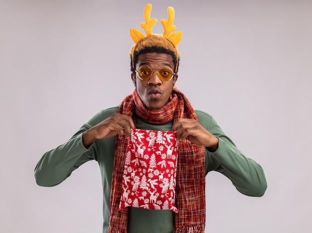 Homme afro-américain avec jante drôle avec des cornes de cerf et une écharpe autour du cou tenant un sac de père noël rouge avec des cadeaux regardant la caméra surpris debout sur fond blanc