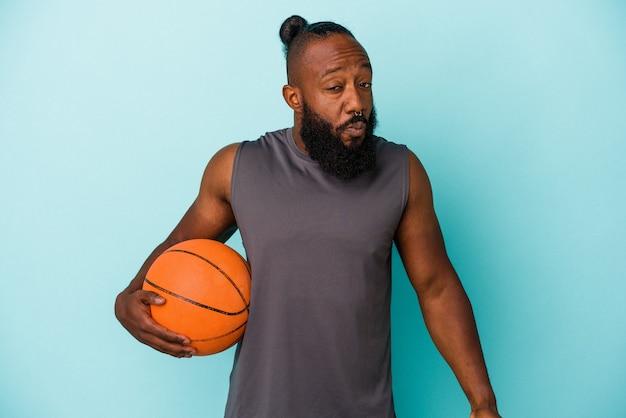 Un homme afro-américain jouant au basket-ball isolé sur fond bleu hausse les épaules et ouvre les yeux confus.