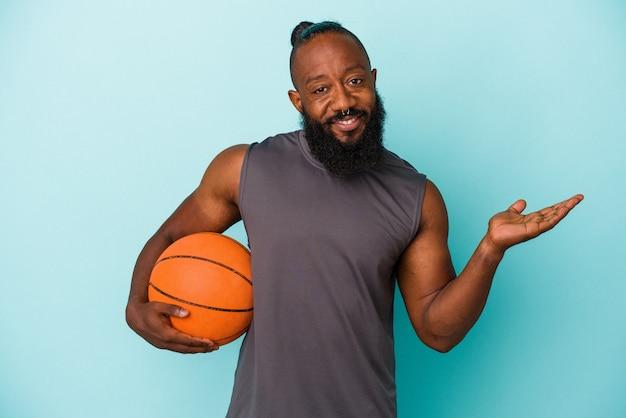 Homme afro-américain jouant au basket-ball isolé sur fond bleu montrant un espace de copie sur une paume et tenant une autre main sur la taille.