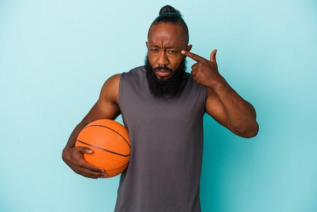 Homme afro-américain jouant au basket-ball isolé sur fond bleu montrant un geste de déception avec l'index.