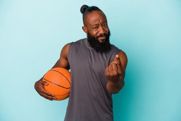 Homme afro-américain jouant au basket-ball isolé sur fond bleu pointant du doigt vers vous comme s'il vous invitait à vous rapprocher.