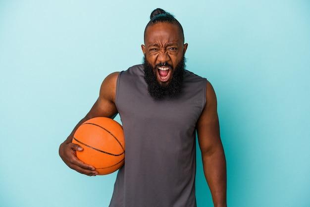 Homme afro-américain jouant au basket-ball isolé sur un mur bleu criant très en colère et agressif.