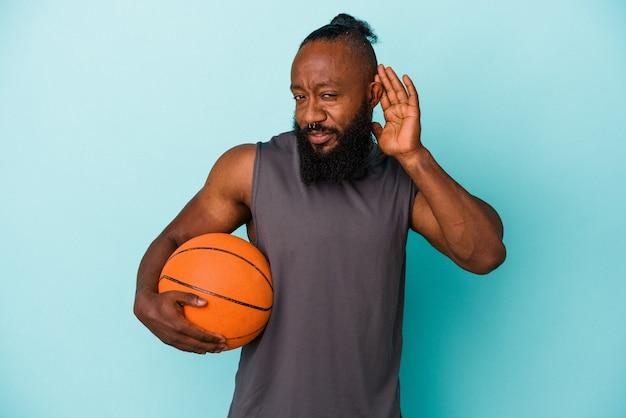 Homme afro-américain jouant au basket-ball isolé sur un mur bleu essayant d'écouter un potin.