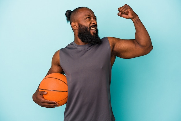 Homme afro-américain jouant au basket-ball isolé sur un mur bleu levant le poing après une victoire, concept gagnant.