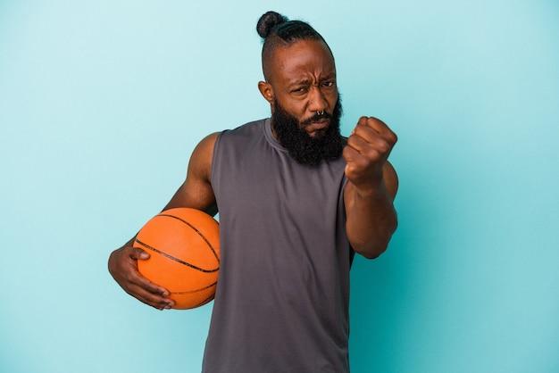 Homme afro-américain jouant au basket-ball isolé sur un mur bleu montrant le poing à la caméra, expression faciale agressive.