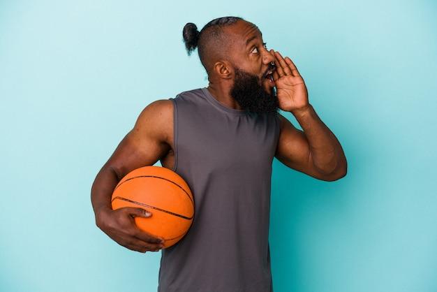 Homme afro-américain jouant au basket isolé sur fond bleu criant et tenant la paume près de la bouche ouverte.