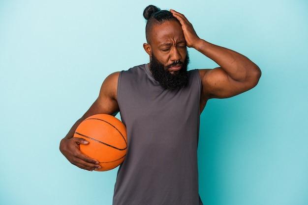 Homme afro-américain jouant au basket isolé sur fond bleu étant choqué, elle s'est souvenue d'une réunion importante.