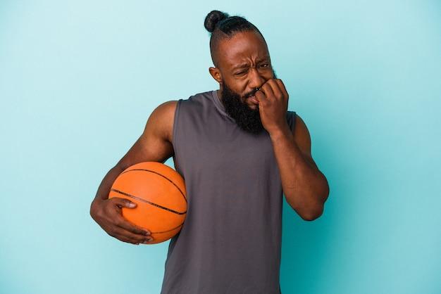 Homme afro-américain jouant au basket isolé sur fond bleu se ronger les ongles, nerveux et très anxieux.