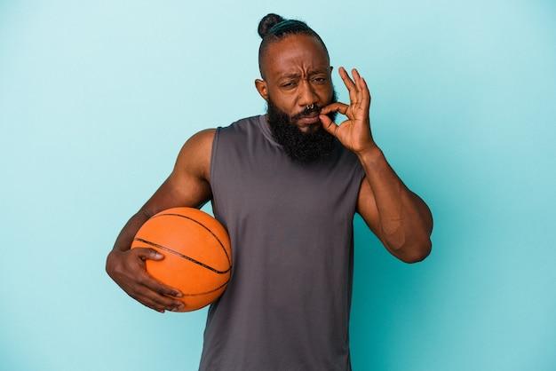 Homme afro-américain jouant au basket isolé sur un mur bleu avec les doigts sur les lèvres gardant un secret.