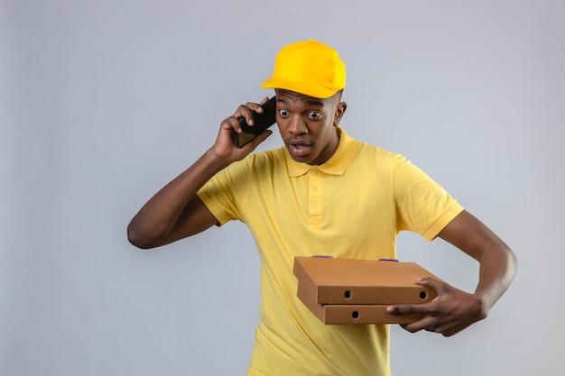 Homme afro-américain de livraison mécontent en polo jaune et casquette tenant des boîtes à pizza choqué de parler au téléphone mobile