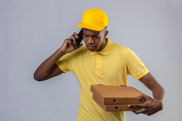 Homme afro-américain de livraison mécontent en polo jaune et casquette tenant des boîtes de pizza tout en parlant au téléphone mobile