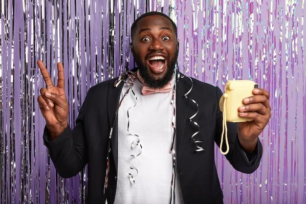 Un homme afro-américain mal rasé montre un geste de paix, se tient devant une petite caméra pour faire un portrait selfie, porte un costume élégant, pose contre un mur de guirlandes violettes. hé, viens à notre fête bruyante!