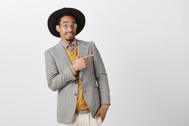 Un homme afro-américain maladroit et mécontent s'incline et grince des dents, pointant le coin supérieur droit quelque chose d'effrayant