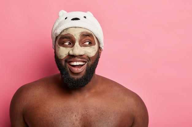 Homme afro-américain avec masque d'argile, exprime des émotions positives isolées