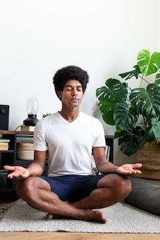 Un homme afro-américain médite dans son appartement espace de copie image verticale méditationspiritualité