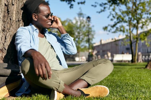 Homme afro-américain noir dans des vêtements élégants, assis les jambes croisées près de l'arbre au parc verdoyant, bavardant sur son téléphone portable, regardant de côté avec une expression heureuse, admirant le temps splendide à l'extérieur