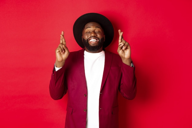 Homme afro-américain plein d'espoir faisant un vœu, tenant les doigts croisés pour la bonne chance et souriant optimiste, debout sur fond de fête rouge