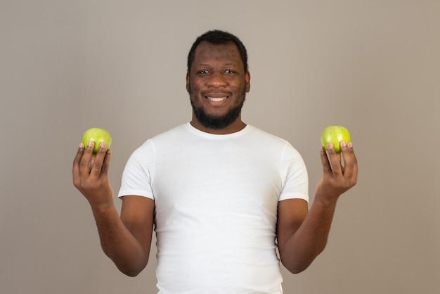 Homme afro-américain avec une pomme dans les deux mains, debout devant le mur gris.