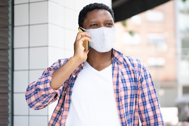 Homme afro-américain portant un masque facial et parler au téléphone tout en marchant à l'extérieur dans la rue. nouveau concept de mode de vie normal.