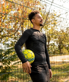 Homme afro-américain posant avec un ballon de foot sur un terrain