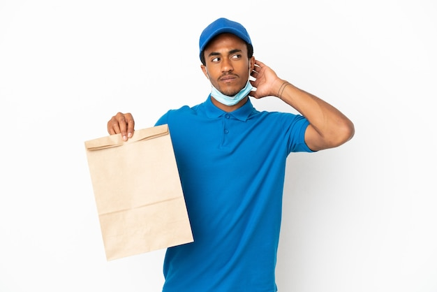 Homme afro-américain prenant un sac de nourriture à emporter isolé sur fond blanc ayant des doutes