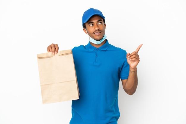 Homme afro-américain prenant un sac de nourriture à emporter isolé sur fond blanc pointant vers une excellente idée