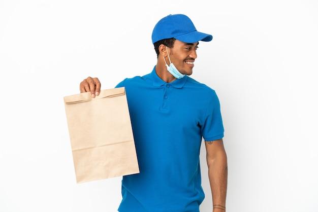 Homme afro-américain prenant un sac de nourriture à emporter isolé sur fond blanc regardant sur le côté et souriant