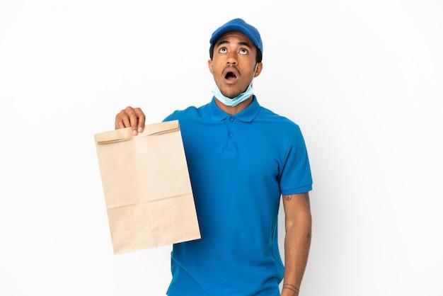 Homme afro-américain prenant un sac de plats à emporter isolé sur fond blanc en levant et avec une expression surprise