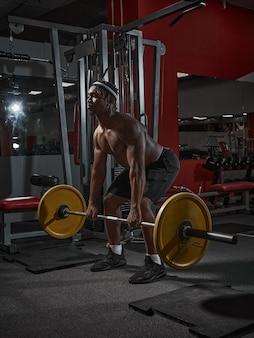 Un homme afro-américain puissant s'accroupit avec une barre pendant l'entraînement en force au poids de la salle de sport