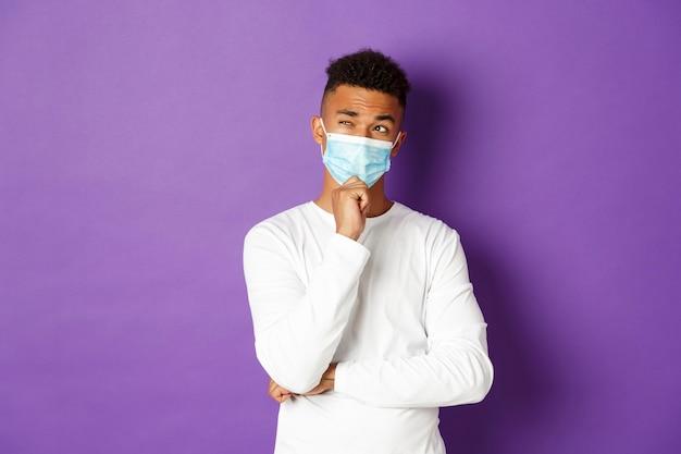 Homme afro-américain réfléchi en masque médical sur violet