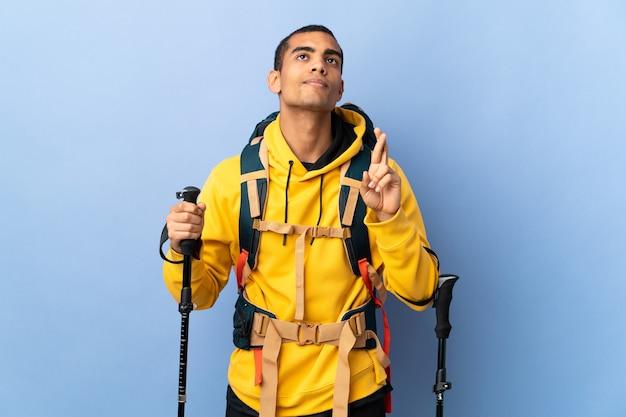 Homme afro-américain avec sac à dos et bâtons de randonnée avec les doigts qui se croisent et souhaitant le meilleur
