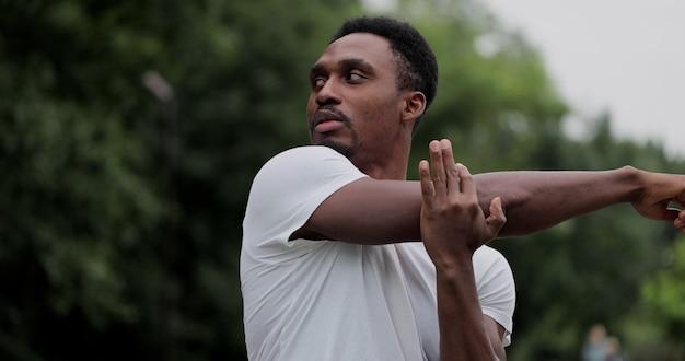 Un homme afro-américain se réchauffe et s'étire dans le parc à l'extérieur pour s'entraîner
