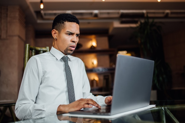 Homme afro-américain sérieusement surpris par ce qu'il voit sur son ordinateur portable, dans une chemise blanche, à l'intérieur