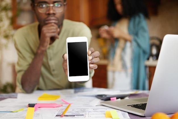 Homme afro-américain sérieux portant des lunettes tenant un téléphone mobile