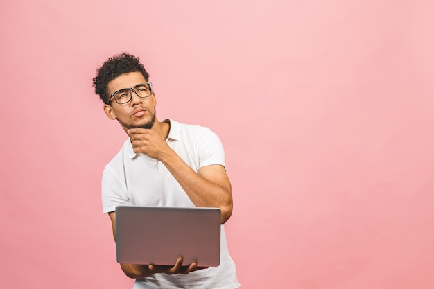 Homme afro-américain sérieux réfléchi avec ordinateur portable isolé sur fond rose