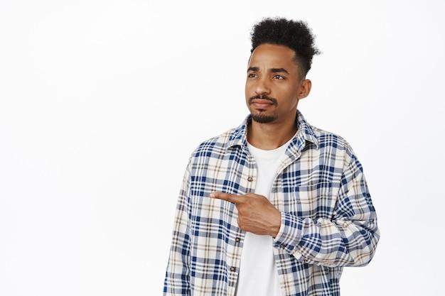 Homme afro-américain sérieux et réfléchi, pointant et regardant à gauche la bannière du logo de vente, fronçant les sourcils sombre et pensif, debout sur blanc