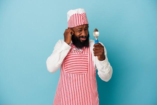 Homme afro-américain de sorbetière tenant une boule de crème glacée isolée sur fond bleu couvrant les oreilles avec les mains.
