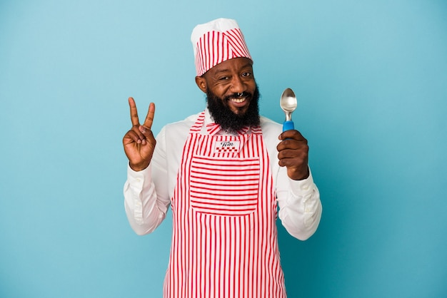 Homme afro-américain de sorbetière tenant une boule de crème glacée isolée sur fond bleu montrant le numéro deux avec les doigts.